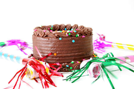 cake with icing: Chocolate birthday cake with sprinkles and noise makers all isolated on a white background