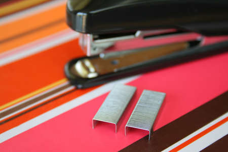 office stapler: Close up with a shallow DOF of staples and a stapler in the background, all on a very colorful notebook.