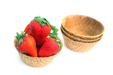 Fresh strawberries in a waffle cone bowl isolated on a white background.