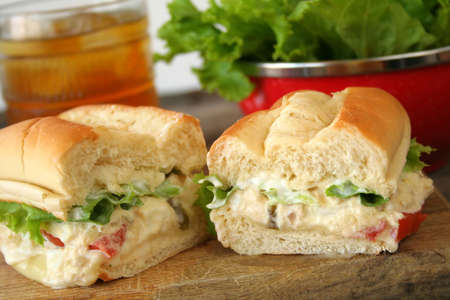 Fresh tuna salad sandwich on a hoagie roll with ice tea and a bowl of lettuce in the background.