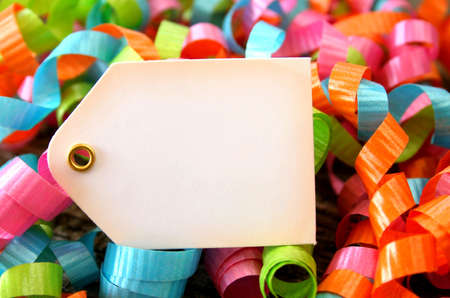Colorful ribbons surrounding a blank tag. Stock Photo