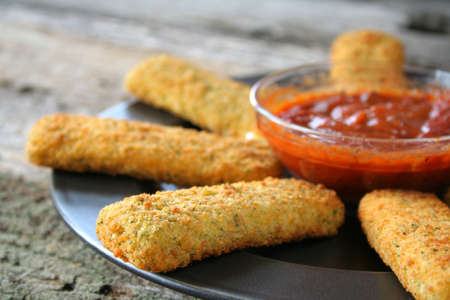 Appetizer of mozzarella cheese sticks with marinara sauce. Used a shallow depth of field.