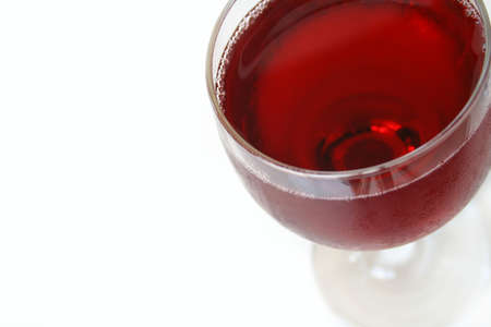 Red wine, macro view with focus on both sides of the lip of glass and very front of glass. Isolated on white with copy space.