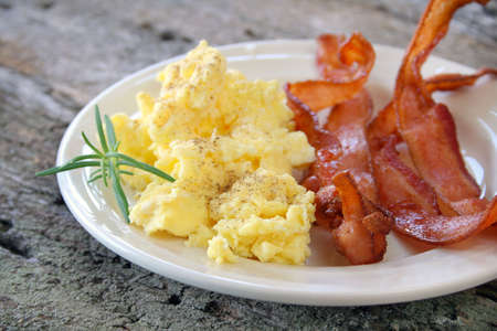 Scrambled eggs with crispy bacon on a plate, and garnished with a fresh sprig of Rosemary.