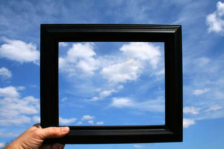 A person holding up a picture frame against a beautiful blue sky full of clouds.