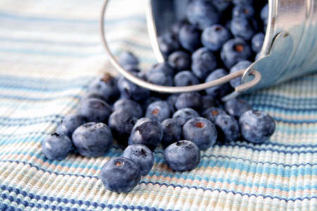 Close up of blueberries spilling out of a bucket onto a matching mat. Zdjęcie Seryjne
