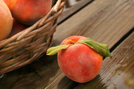 Close up of a peach with leaves attached. 免版税图像