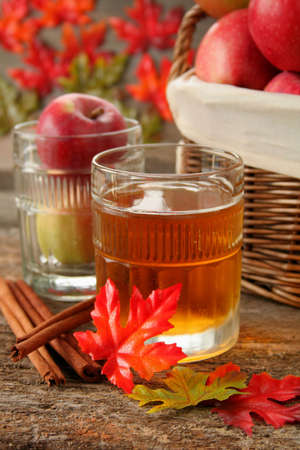 A glass of apple juice with fresh apples, fall leaves and cinnamon sticks make up this beautiful image.