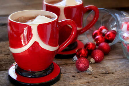 Two cups of hot chocolate with marshmallow creme and Christmas ornaments laying to the side.