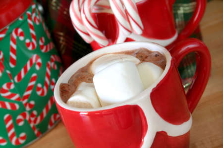 Close up of marshmallows in a cup of hot chocolate with a Christmas theme.