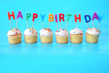 Cupcakes with Happy Birthday Candles on them against a blue background and plenty of room for copy space. Stock Photo