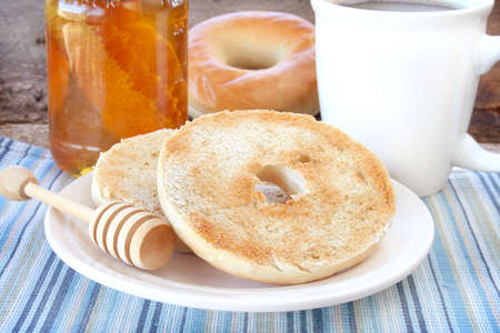 Bagel and honey for breakfast with a cup of coffee.