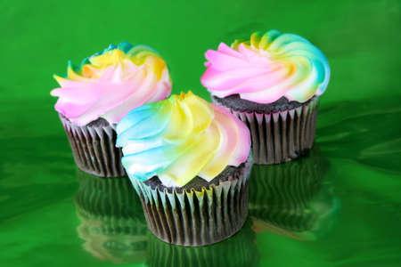 metalic: Three multi colored cupcake of chocolate shot on a metalic green background.