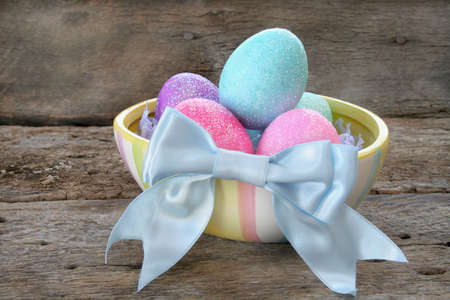 colo: Colorful Easter eggs in a dish with a blue bow.