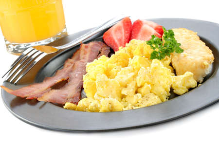 oj: Scrambled eggs, bacon, hash browns along with fruit with oj in the background. Stock Photo
