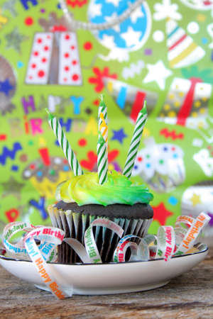 One cupcake with candles and birthday ribbons.  Used a shallow depth of field and selective focus. photo