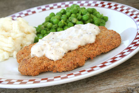 Country fried steak with gravy and side dishes of mashed potatos and fresh peas.
