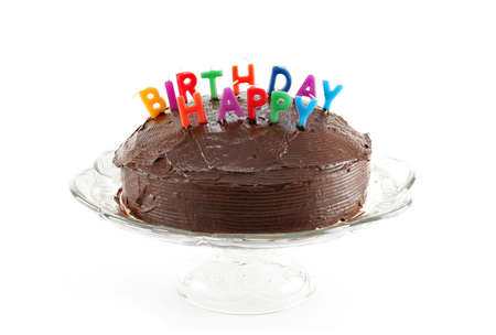 Chocolate cake with candles that spell out HAPPY BIRTHDAY on a cake plate on a white background. Zdjęcie Seryjne