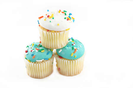 Three cupcakes with blue and white icing and sprinkles against a white background with room for text. photo