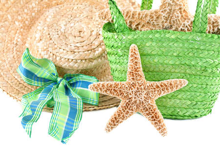 Starfish leaning against a green beach bag and a womans hat with a blue and green bow.  Concept is summer fun while at the beach.