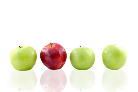 incompatible: Three green apples and one red apple lined up on a white background with a reflection. Room for text. Stock Photo