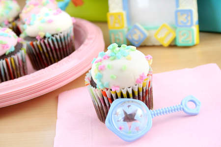 One cupcake with white icing and pastel sprinkles with a baby rattle.  Concept is for a baby shower and a childs birthday party.
