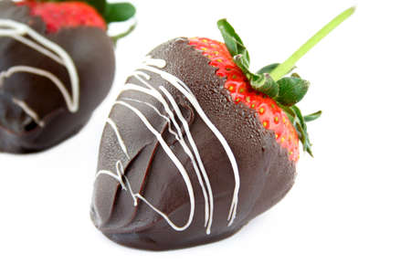 Close up of a chocolate covered strawberry on a white background with another strawberry out of focus in the back. Used a shallow depth of field and selective focus.