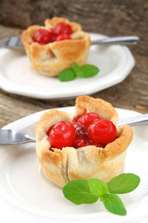Two mini cherry piestarts on white plates garnished with mint leaves. photo