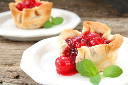 Mini individual cherry tartspies on white plates and garnished with mint leaves.  Used a wood textured background for a rustic look. photo