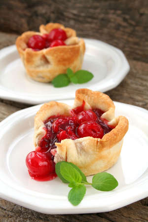 Two mini cherry piestarts on white plates garnished with mint leaves.