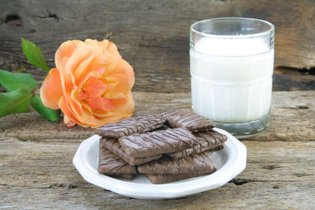 chocolaty: Saucer  full of chocolate covered cookies with a glass of milk in the background along with a single rose.