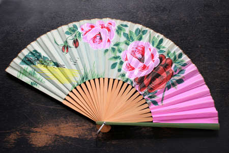 asian art: Oriental fan that is very colorful and shot on an old wood table. Stock Photo