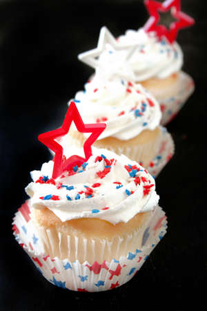 Cupcakes with white icing and star sprinkles along with a star shape decoration. photo