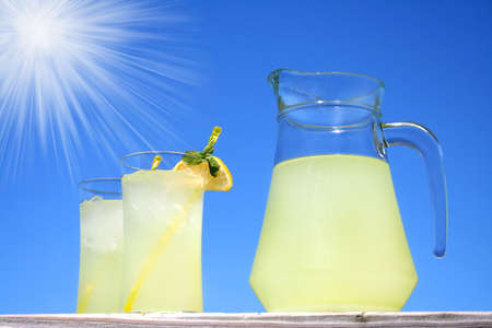 Glasses of lemonade outside with a bright blue sky and sun with sun rays. Stock Photo