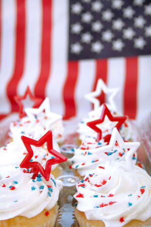 Cupcakes decorated in a patriotic theme with the American flag as a background.  Shot with a shallow depth of field and selective focus and room for text.