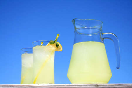 Two glasses of lemonade along with a pitcher of lemonade outside with a beautiful blue sky as the background and room for text.