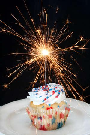 Quatrième de cupcake Juillet fait avec étoile rouge et bleu en forme de Sprinkles et un feu d'artifice Sparkler comme la chandelle. Banque d'images - 5058729