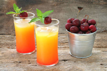 Tequila Sunrise Juice drink with fresh cherries and mint leaves shot on a rustic looking background.