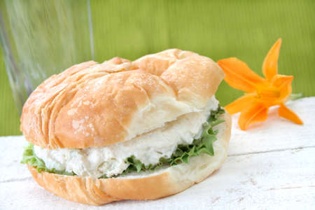 Chicken salad croissant sandwich with a drink and day lilly in the background and room for text. Фото со стока - 5122294