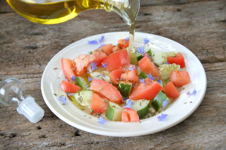 corn flower: Fresh tomato and cucumber salad with dried parsley and edible corn flower with a dressing being pourded. Stock Photo