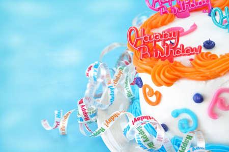 La metà di una torta di compleanno con le parole come un felice compleanno decorazione sulla parte superiore della torta. Nastri sono circostante il fondo della torta che dire Buon Compleanno. Camera per il testo.