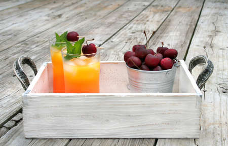 serving tray: Two drinks garnished with fresh mint and cherries on a wooden serving tray shot outside.