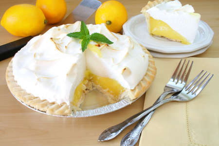 Lemon Meringue pie with a slice cut out and served on a plate, surrounded by fresh lemons and forks. photo
