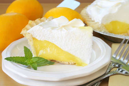 Close up of a slice of lemon meringue pie garnished with fresh mint leaves. In the background there is lemons and the pie that the slice came from.
