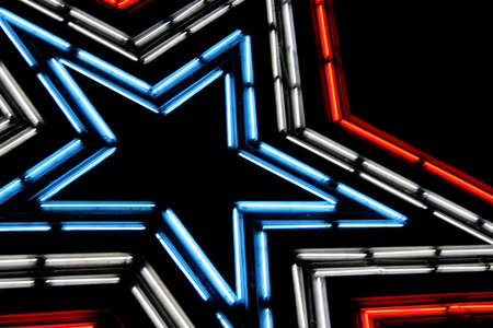 Large neon lit star with patriotic colors of red, white and blue.  Shot against the night sky. Stock Photo