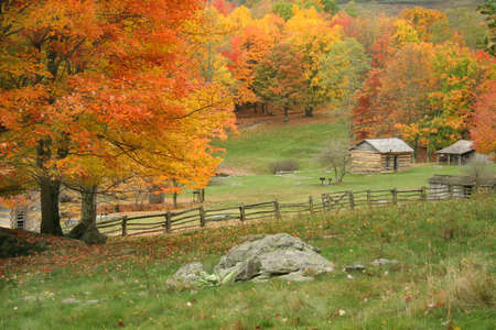 View of some fields along with a split rail fence with a cabin in the distance.  Taken during peak of Autumn.