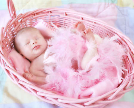 Sweet baby girl covered in pink feathers and inside a pink basket.  Peaceful look on her face.