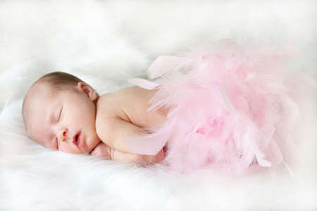sleeping infant on white with pink feathers covering her bottom.