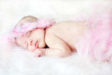 Sweet sleeping baby on a white blanket with a head piece around her head and pink feathers over the bottom part of her body.