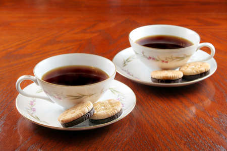 low light: Two cups of hot coffee with a snack of cookies.  Low light used for mood. Stock Photo